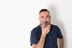 Caucasian hipster with a large gray beard 40-45 years old, on white background looking straight ahead with his hand fixing his beard