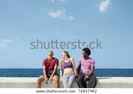 caucasian, hispanic and african american friends smiling and having fun near the sea. Horizontal shape, three quarter length, copy space