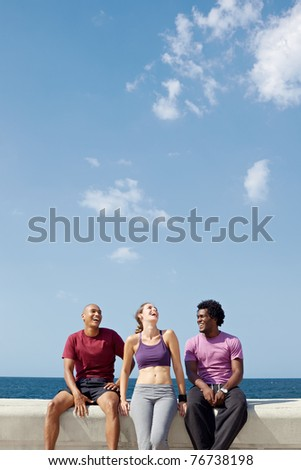 caucasian, hispanic and african american friends smiling and having fun near the sea. Vertical shape, three quarter length, copy space