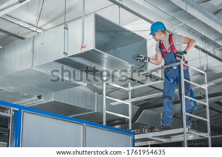 Caucasian HVAC Technician Worker in His 40s Testing Newly Installed Warehouse Ventilation System. Commercial Heating, Cooling and Air Ventilation Systems.