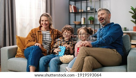 Caucasian joyful happy Caucasian family resting at home watching TV together sitting on couch with popcorn and laughing. Mom and dad with small son and daughter eating popcorn watching comedy movie
