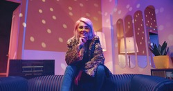 Caucasian joyful stylish beautiful Caucasian woman with blonde hair in yellow glasses wearing fur coat sitting on the back of couch in living room in neon disco light, looking at camera and smiling