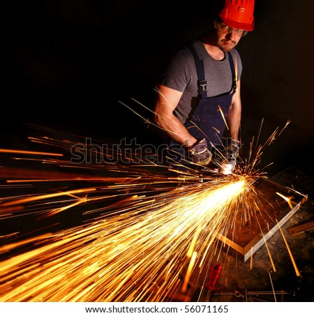 caucasian labor work with electric grinder on metal part