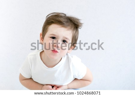 Caucasian little boy with stomach ache, child holding his hands on his belly. Stomach ache child stock image.