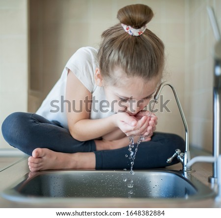 Caucasian little girl drinking from water tap or faucet in kitchen. Hands open for drinking tap water. Pouring fresh healthy drink. Good habit. Right choice. Environment concept. World Water Day