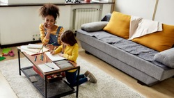 Caucasian little girl spending time with african american baby sitter. They are drawing, learning to write letters, sitting on the floor. Children education, leisure activities, babysitting concept