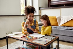 Caucasian little girl spending time with african american baby sitter. They are drawing, learning how to draw, sitting on the floor. Children education, leisure activities, babysitting concept