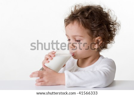 Caucasian little girl, 5-6 years old, curly hair, drinking a glass of milk, isolated on white background