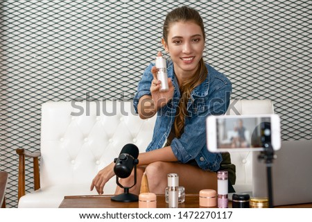 caucasian makeup artist youtuber influencer broadcasting demonstrating her cosmetic product live online