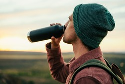 Caucasian male adventurer wearing beanie hiking in mountain quenching thirst drinking water