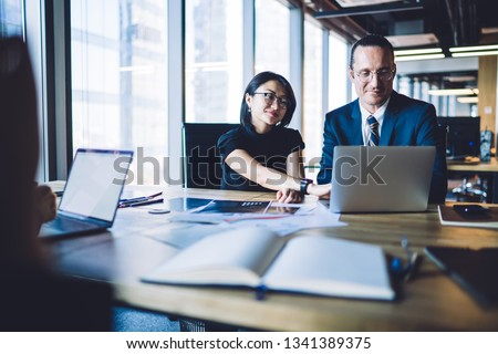 Caucasian male and asian female partners sitting with laptop computer at meeting table,business people collaborating on project using technology.  Two office employees brainstorming and collaborating