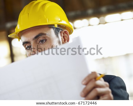 caucasian male architect examining blueprints. Horizontal shape, head and shoulders, front view, copy space