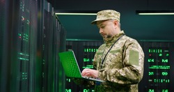 Caucasian male army technician in camouglage costume and hat typing on keyboard of laptop computer while working with secret data at server room. Government analytic center.