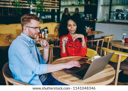 Caucasian male caucasian entrepreneur showing application on modern laptop computer african american professional manager during meeting in cafeteria using free internet connection #1141048346