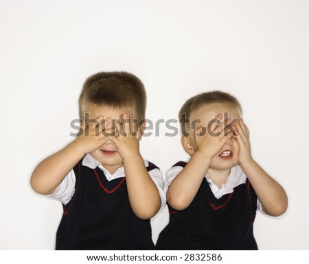 Caucasian male children twins with hands over eyes.