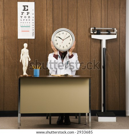 Caucasian male doctor sitting at desk holding clock over face.