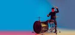 Caucasian male drummer improvising isolated on blue studio background in neon light. Performing, looks inspired, energy. Concept of human emotions, facial expression, ad, music, art, festival. Flyer.