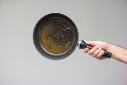 Caucasian male hand holding an old frying pan stained with brown burned oil and grease isolated on gray.