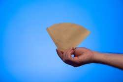 Caucasian male hand holding an unused brown paper coffee filter studio shot isolated on blue background.