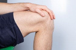 Caucasian male leg bent in knee. Hand laying on leg. White background.