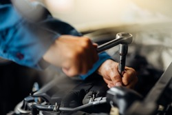 Caucasian male mechanic repairs car in garage. Car maintenance and auto service garage concept. Close up mechanical hand and spanner.