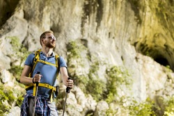Caucasian male model with backpack hiking on sunny day