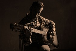 Caucasian male musician playing guitar on stage, focus on hand. sepia.
