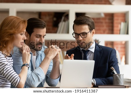 Caucasian male real estate agent or broker consult couple clients show project on laptop screen. Man realtor or financial advisor talk have consultation with spouses at office meeting. Rental concept. Foto stock ©