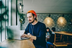 Caucasian male resting in coffee shop listening favorite music in headphones and chatting in social networks, skilled freelancer enjoying remote job typing publication for web blog on laptop