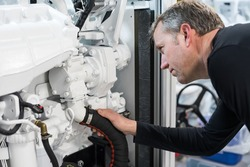 Caucasian Male Superyacht Engineer working on the engine room, inspecting the generator