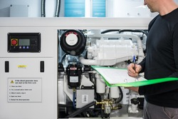 Caucasian Male Superyacht Engineer working on the engine room, inspecting the generator with checklist folder and pen in his hand