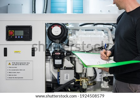 Caucasian Male Superyacht Engineer working on the engine room, inspecting the generator with checklist folder and pen in his hand Foto d'archivio ©