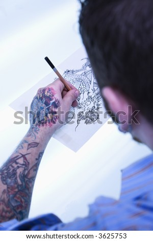stock photo : Caucasian male tattoo artist drawing tattoo on light table.