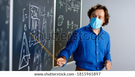 Caucasian male teacher in medical mask standing at board in classroom and telling physics or geometry laws to class. Pandemic concept. School during coronavirus. Educative mathematics lection.