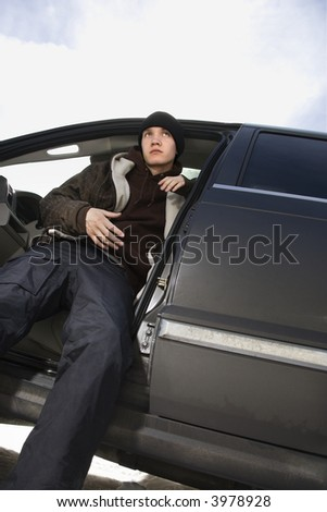 Caucasian male teenager sitting in SUV.