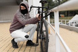 Caucasian male Thief in balaclava and hood breaks the lock on a bicycle in the street during the day. Closed face and hacking. Stealing bicycles.