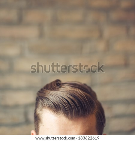 Caucasian male with hipster haircut against brick wall. Top of the head. Unrecognizable person.