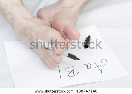 Caucasian male writing alphabet using bare foot.