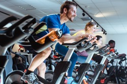 Caucasian man and friends on fitness bike in gym during workout