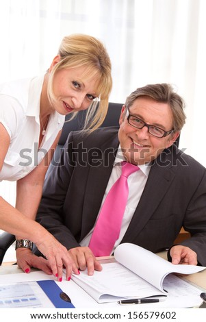 Caucasian man and woman looking at camera in office.