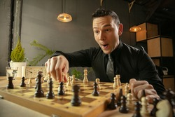 Caucasian man chess player sitting at home and playing chess alone.