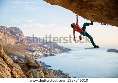 Caucasian man climbing challenging route going along ceiling in cave at sunset, against beautiful evening view