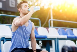 Caucasian man drinking water with his eyes closed after exercises