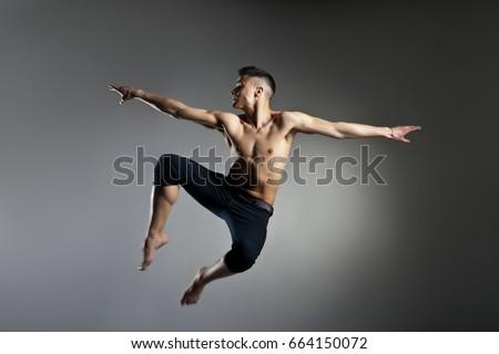 Caucasian man gymnastic leap posture on grey background #664150072