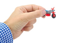 Caucasian man hand holding a plastic bicycle toy on white background