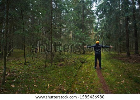 Caucasian man has a walk in spruce forest, enjoying enviroment