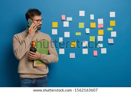 Caucasian man has creative approach to organizing work, leaves colorful stickers on wall, discusses working schedule with partner via smartphone, drinks takeaway coffee, holds textbooks and diary