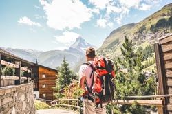 Caucasian man hiking in beautiful Zermatt, Switzerland. Matterhorn in background. Backpacking lifestyle concept. Adventure, outdoor. Summer Alps, Europe. Travel, traveler