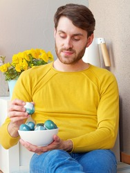 Caucasian man holding a blue easter eggs in a bowl during easter time, colored with natural red cabbage coloring, wearing a yellow sweather with yellow flowers in the background in the balcony.