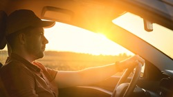 Caucasian Man in automobile in the countryside and sun rays. Male driver driving a car at sunset background. Summer travel, road trip and vacations concept. Side view